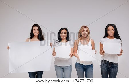 We are all human. Wonderful attractive fearless ladies standing close to each other and holding blank posters while posing isolated on white background
