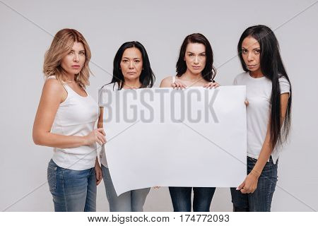 Call to action. Serious independent diverse ladies uniting for a cause while holding up a pig blank poster and posing in a similar clothes