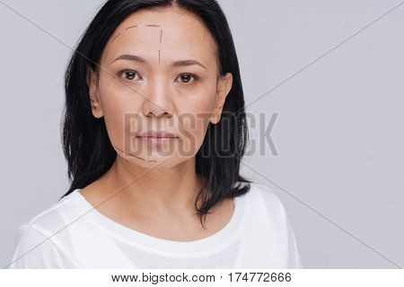 Rendering the face. Enigmatic genuine captivating woman acting as about making a plastic surgery while working on social advertisement promoting natural beauty