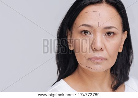 Follow the guidelines. Serious natural gorgeous lady posing for a photographer standing isolated on white background while working on social advertisement