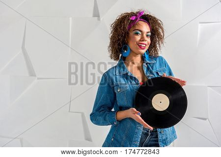 Waist up portrait of Cheerful young woman with curly hair keeping gramophone record in arm. Copy space
