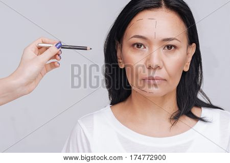 Total makeover. Neat young Asian lady standing still isolated on white background while someone drawing guidelines on her face using special pencil
