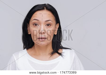 Just a little touch. Pleasant young Asian lady posing for a photographer wearing special surgery guidelines on her face and standing isolated on white background