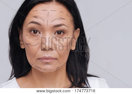 Not enough. Inspired beautiful sensual woman working on social advertisement promoting natural beauty while posing with special marks on her face