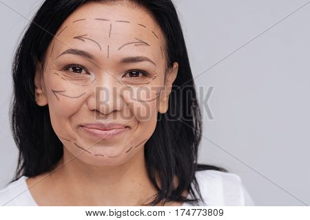 You do not need that. Healthy looking Asian lady demonstrating pre surgery guidelines on her face while smiling and standing isolated on white background