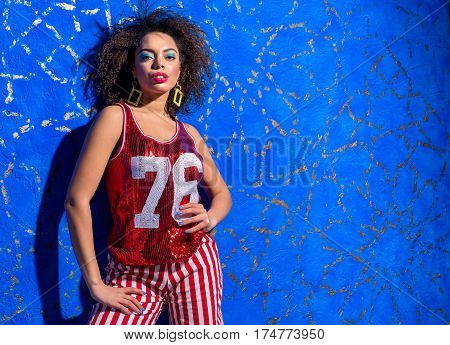 Portrait of serene african female posing with curly hair wearing in tank top with sequins. Copy space