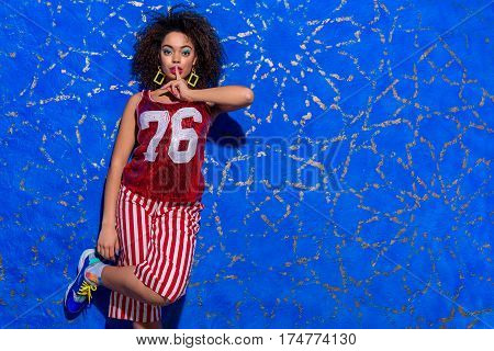 Keep calm. Cheerful young woman touching lips by finger while leaning against blue wall. Copy space