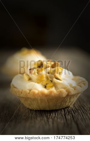 Delicious mascarpone tartlet with pictachios on wooden table