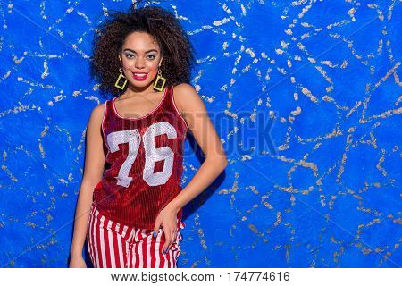 Attractive outgoing african lady standing with curly hair and with bright makeup near blue wall. She is smiling, Copy space
