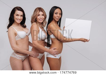 Having each others backs. Confident resolute sensual ladies demonstrating diverse body types while working on natural beauty campaign and holding a blank sign