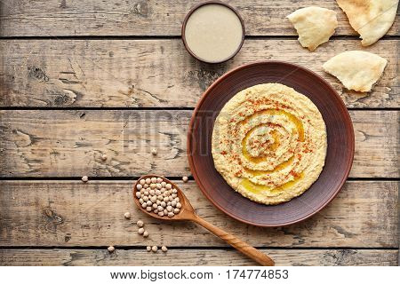 Hummus eastern homemade snack chickpea vegan natural nutrition lunch dip paste with pita bread paprika tahini and olive oil in clay plate on rustic flat lay. Healthy dietary fiber protein food