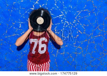 Female holding music platter in front of her face while standing near blue wall. Copy space
