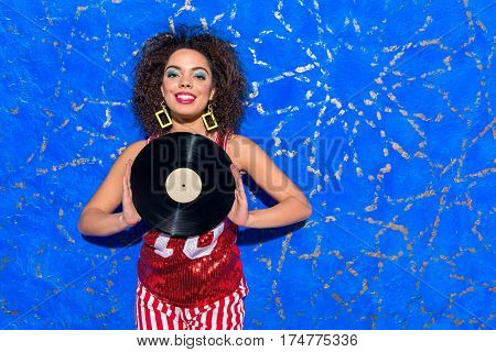 Portrait of Cheerful woman with blue makeup dancing while keeping gramophone record in arms. Copy space