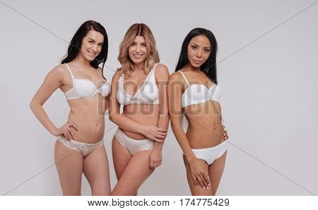 Curvy and elegant. Motivating confident brilliant ladies posing for a photographer in their underwear while working on body beauty campaign together
