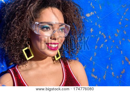 Happy african female standing with festive colors look and with different accessories. Disco style. Copy space