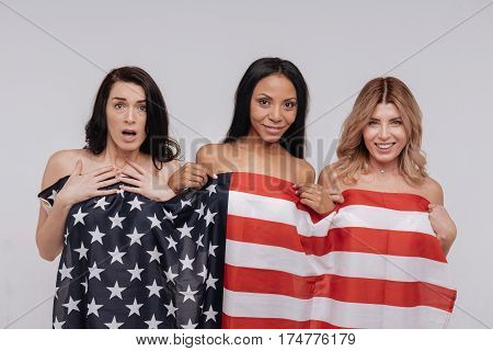 Oops. Hot hilarious graceful women covering their bodies using a flag while working on set of professional photoshoot