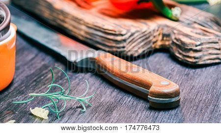 Rosemary, kitchen knife  and red paprika on rustic board and dark wood table. Close-up