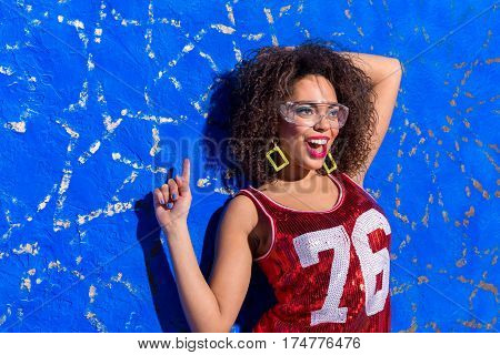 Disco is my life. Outgoing african female flourishing arms while dancing near blue background. Copy space