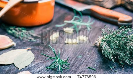 Thyme and rosemary twigs, bay leaf, fusilli, kitchen knife and ceramic pan on black table. Close-up