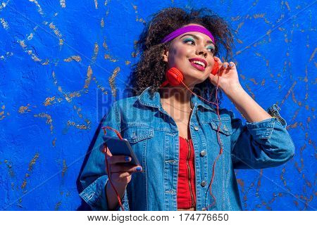 Portrait of Happy young woman listening music through headphones while keeping mobile phone in arm