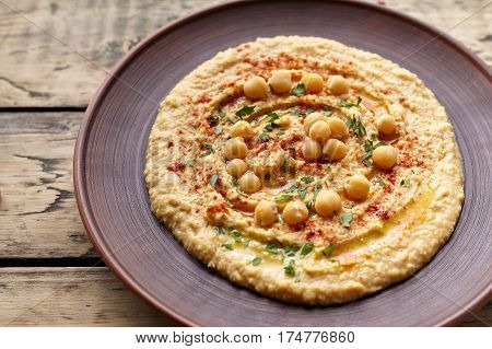 Hummus traditional homemade creamy chickpea vegan natural nutrition dip paste with paprika tahini parsley and olive oil in clay plate on rustic flat lay. Healthy dietary fiber protein food