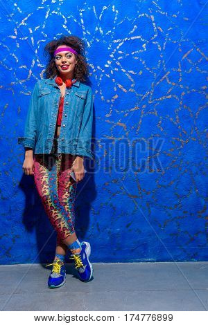 Cheerful african female wearing in retro style holding handset while standing near blue wall. She is smiling. Copy space
