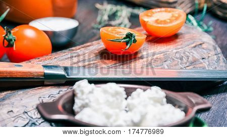 Red cherry tomatoes on wood board and ricotta in ceramic plate on black table. Close-up