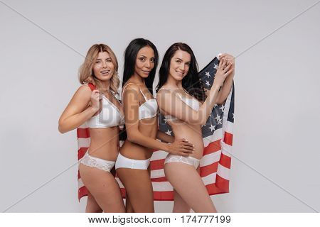 Friendly vibes. Energetic charismatic elegant women posing together and holding a national flag as a background while wearing underwear only