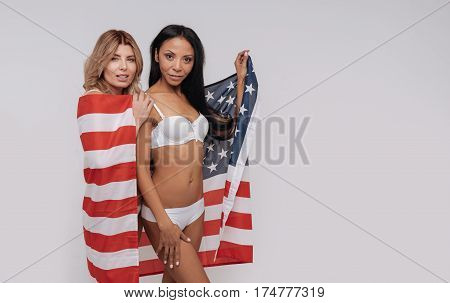 American unity. Charming supportive gorgeous women working closely on a national diversity campaign while wearing their underwear and using a flag as accessory