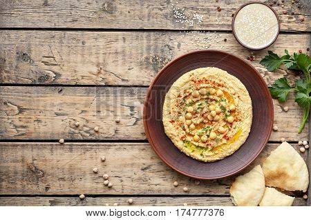 Hummus traditional homemade Israel chickpea vegan natural nutrition dip paste with pita paprika tahini parsley and olive oil in clay plate on rustic flat lay. Healthy dietary fiber protein food