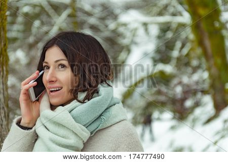 Outgoing young woman is using cell phone while standing in forest covering with snow in Oregon