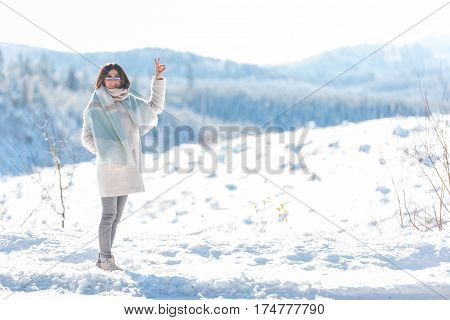 Cheerful female gesturing with hands while situating in white steppe in Oregon