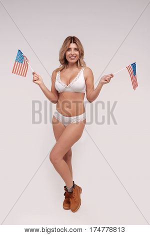 Extraordinary beauty. Pretty proud graceful woman posing in her lingerie and holding national flags in her hands while working for a beauty campaign