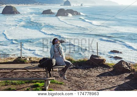 Outgoing young woman sitting on wood table on a background of pleasant view on clear ocean