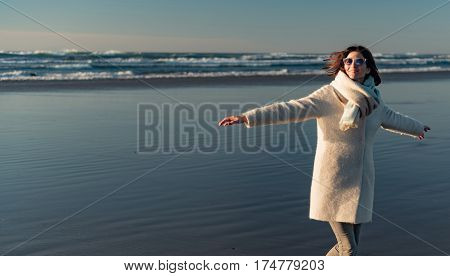 Cheerful young woman swinging arms while standing on coastline near noisy ocean during dusk
