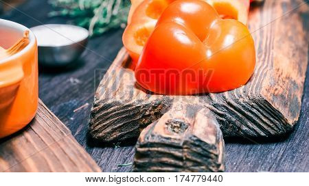 Sliced red paprika, thyme and salt on wood cutting board and on black table. Close-up