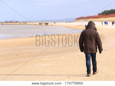 A man strolling on the beach of Swinoujscie Poland.