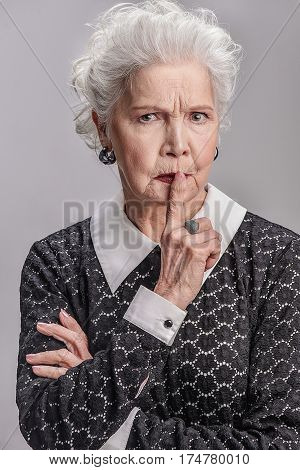 Keep silence. portrait of serious middle aged woman holding her finger on mouth and looking at camera while standing. Isolated on gray background