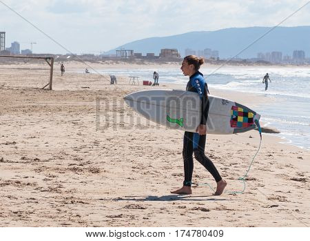 Acre Israel - March 04 2017 : Man in a color waterproof suit walks on the beach and getting ready to start training on board for surfing on the water in Acre beach Israel