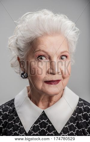 Age is whatever you think it is. Portrait of beautiful elegant elderly lady looking directly at camera while posing against gray background