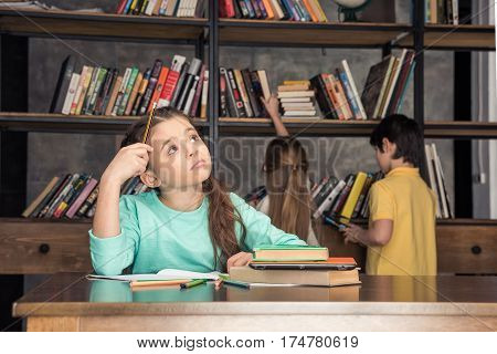 portrait of pensive girl sitting at table with classmates looking for books behind