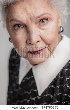 She has lot on her mind. Close up portrait of beautiful elderly female looking at camera while posing on gray background