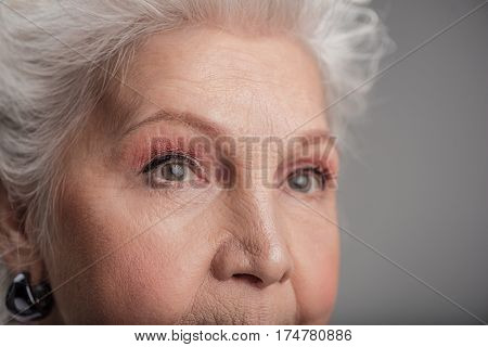 There is time to be serious. Close up of face of elderly lady looking away and thinking about important things, isolated on gray background