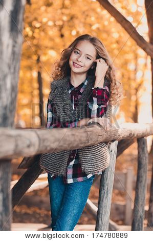 Stylish smiling teen girl 12-14 year old posing outdoors. Wearing casual clothes. Looking at camera. Teenager hood.