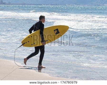 Man In Color Waterproof Suit Walks On Beach With Board