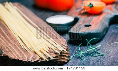 Uncooked spaghetti and red pepper and cherry tomatoes on wood cutting boards and on black table. Close-up