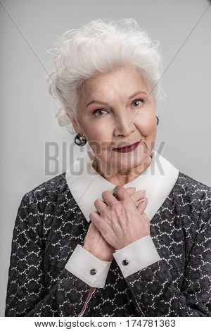 Waist up portrait of beautiful mature woman standing isolated on gray background and looking at camera while folding her arms