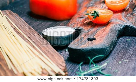 Uncooked spaghetti, red tomatoes and paprika on rustic cutting boards and on black table. Close-up