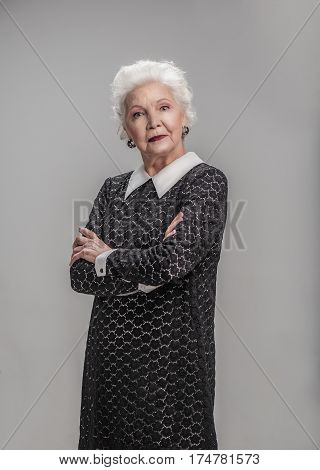 Those were days. Waist up portrait of serious elderly female standing in studio and looking at camera with folded arms. Isolated on gray background