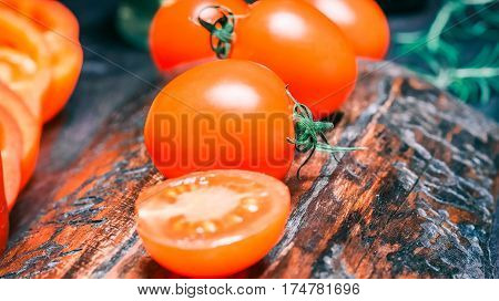 Red fresh cherry tomatoes and red paprika on wood cutting board and on black table. Close-up